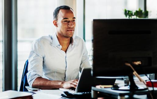 Man sitting at desk looking at a desktop computer working.