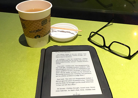 A person reads on an eReader in a coffee shop