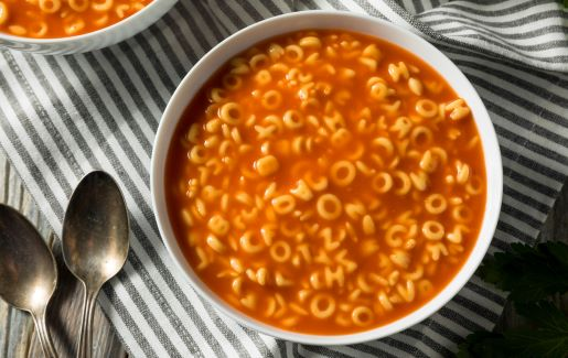 A photo of alphabet Soup on a striped placemat.
