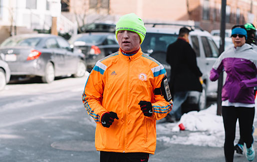 A man wearing a Boston Marathon jacket runs during the winter
