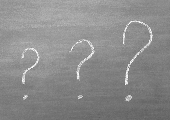 Three question marks drawn on a chalkboard