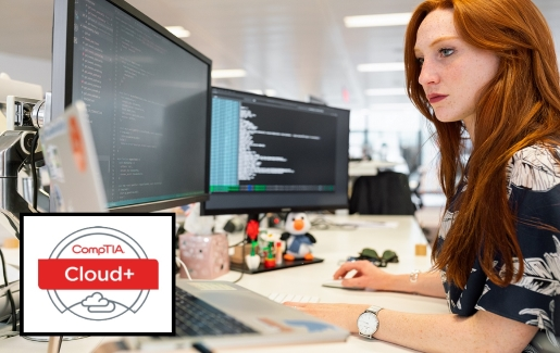 Woman at desk working on coding with 2 monitors and a laptop.