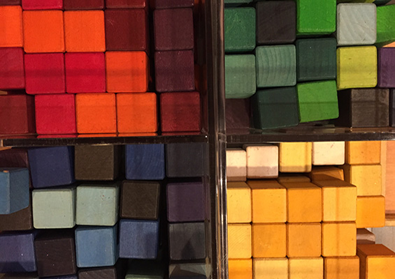 Wooden blocks arranged by color - red, yellow, blue and green.