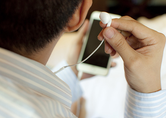 A man puts in ear buds to listen to a podcast