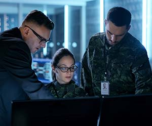 Three military personnel look at a computer screen
