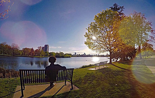A man sits on a bench in a park in Denver