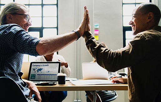Two IT pros high five because they completed a job with knowledge from CompTIA