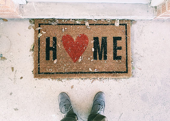 A man stands in front of a door with a welcome mat that says 'Home'