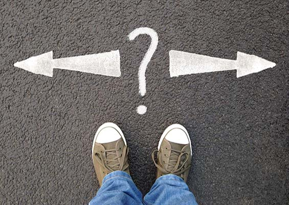 A person stands on a road with arrows pointing in either direction and a question mark.