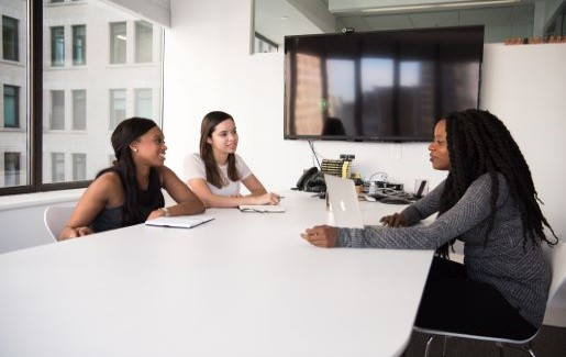 Three women at work in a conference room having a meeting.