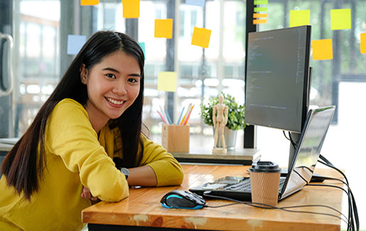 A woman who works in IT smiles while sitting at her desk at work