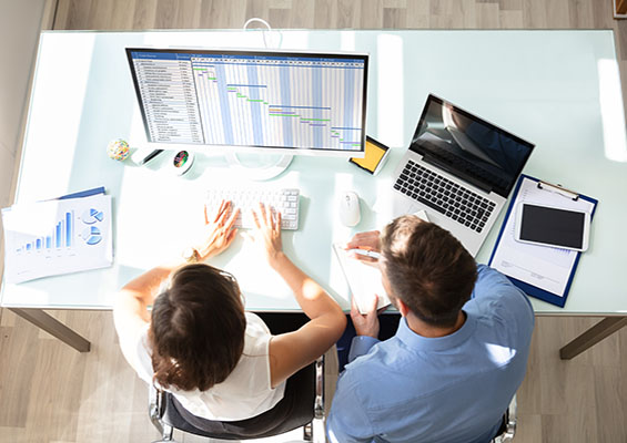 Two IT pros look at a Gantt chart while managing a project