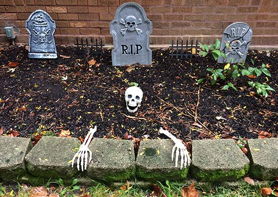 A skeleton coming out of the ground in a graveyard