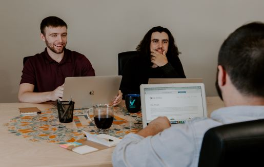 Three men working together on laptops at a table.