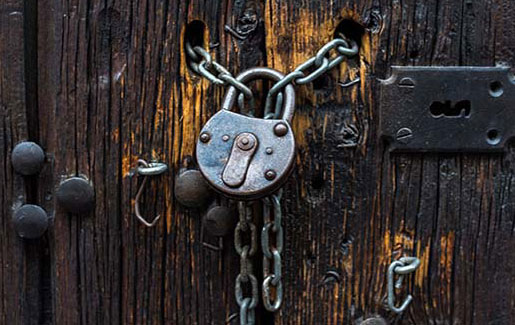 A padlock with lots of chains keeping a wooden door secure