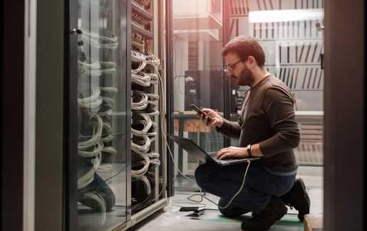 IT professional with a beard and glasses working in a server room.