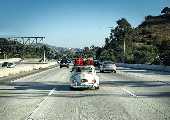 A VW Bug packed up and driving down the highway