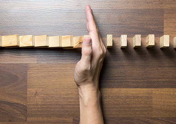 A person puts their hand in a row of dominoes to keep them from falling.