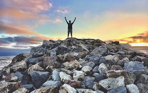 A man stands atop rocks overlooking the Pacific Ocean in San Diego