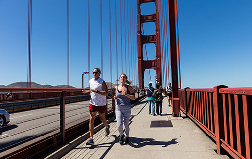 A man and women run across the Golden Gate Bridge in San Francisco