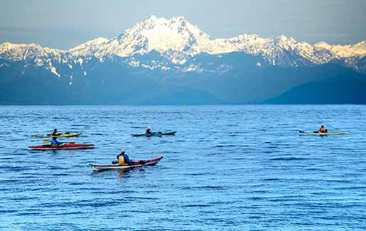 People kayak in Puget Sound in Seattle, looking at Olympic Mountains