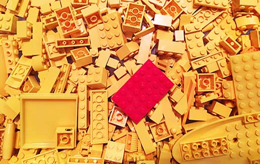 A red Lego in a pile of yellow Legos