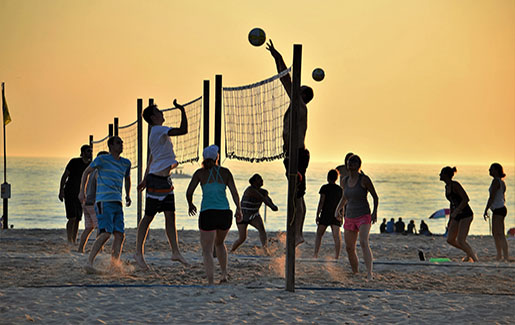 People play beach volleyball at sunset on the beach in Tampa