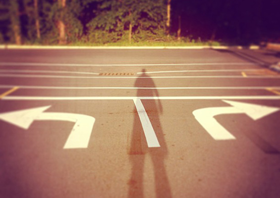The shadow of a person at an intersection with a right turn lane and a left turn lane