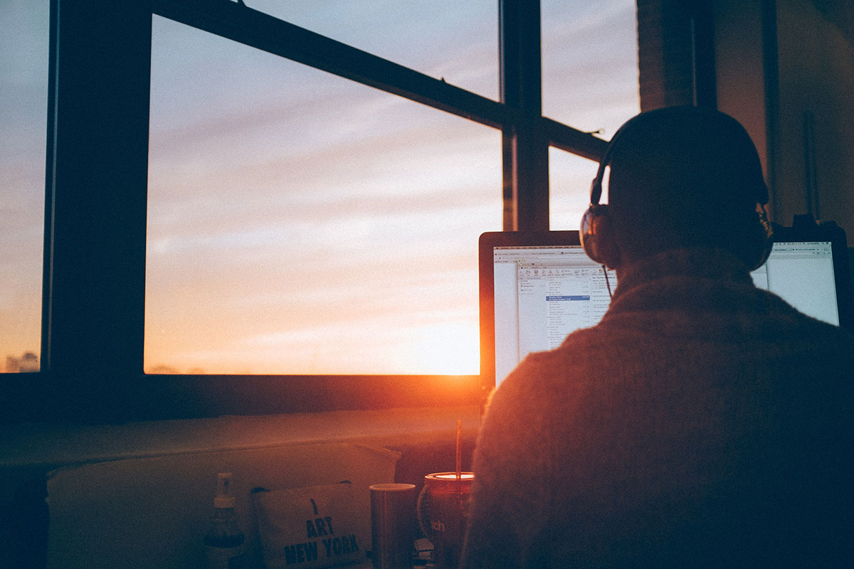 Man working on computer with setting sun behind.