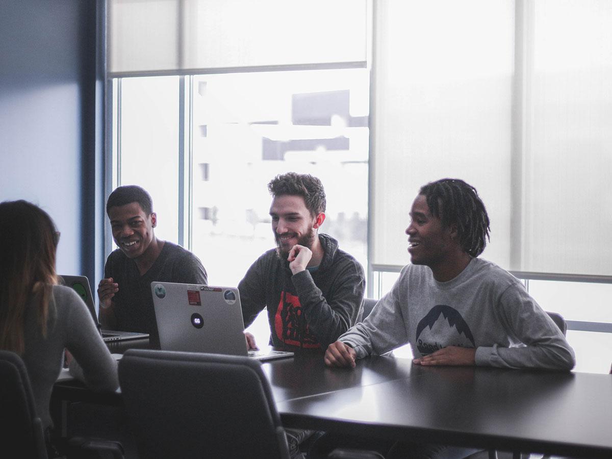 Quatro pessoas se divertindo em uma reunião de trabalho.