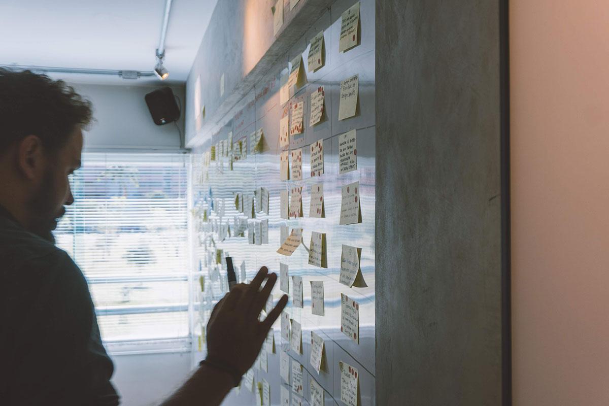 Homem em uma placa branca com notas de post-it.