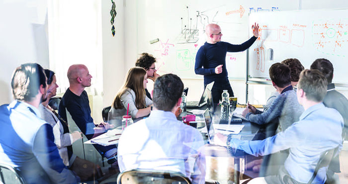 People in a meeting looking at a board
